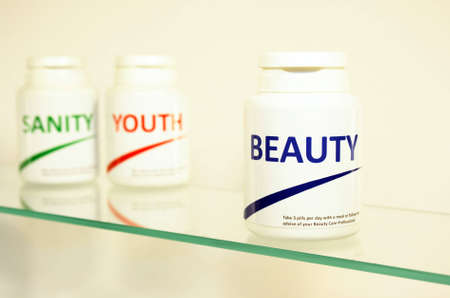 longevity drugs: Sanity, Beauty and Youth pills in a bottle on bathroom shelf with focus on Beauty, fake brands Stock Photo