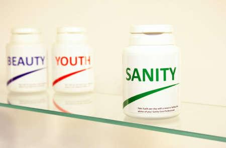 insanity: P�ldoras de la cordura, la belleza y la juventud en una botella en la estanter�a de cuarto de ba�o con enfoque en Sanity, marcas falsas  Foto de archivo