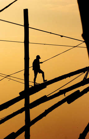 Fisherman walking on a mast in the sunset photo