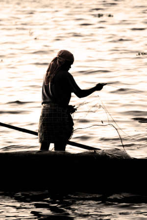 fishingnet: Fisher with her fishingnet in silhouette