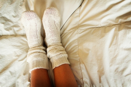 comfortable cozy: Knitted socks in bed on cozy cover Stock Photo