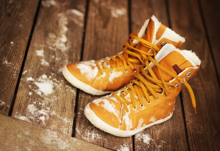 Boots covered with snow on wooden floor