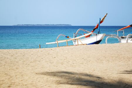 Boat on the beach in asia with island in the far