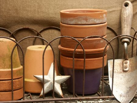 garden stuff: vintage wire basket of stacked terra cotta flower pots, garden trowel, old metal star with olive green background Stock Photo