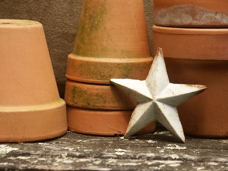garden stuff: vintage metal star leaning against stacked flowerpots on old garden bench