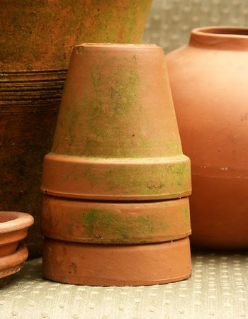 garden stuff: stack of mossy terra cotta flower pots with olive green foreground and background Stock Photo