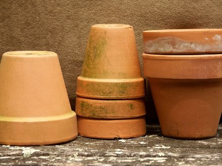 terra cotta: row of stacked terra cotta flower pots with olive green background