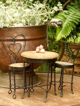 heart shaped stuff: miniature ice cream table and chairs with fern and copper pot Stock Photo