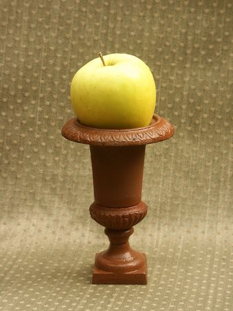 olive green: yellow green apple on pedestal with olive green background