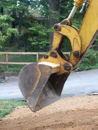 scooping: backhoe scooping up dirt at construction site