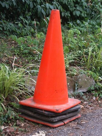 orange construction cone before a leafy background Stock Photo - 1260264