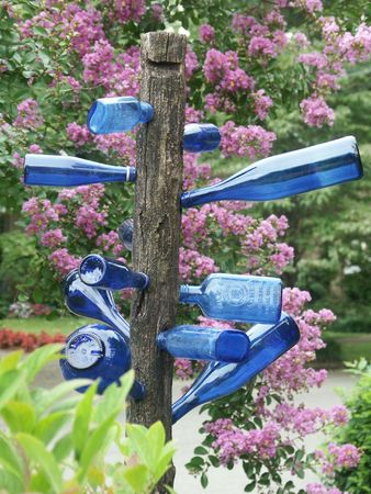 blue glass bottles on folk art bottletree in garden