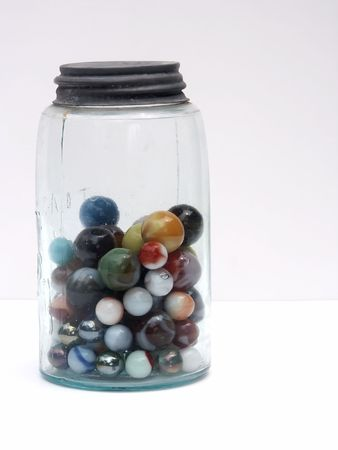marbles in old jar, entire, vertical, white background