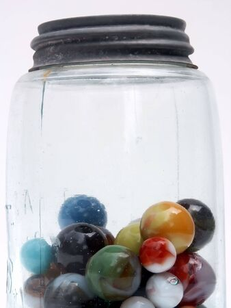 two and two thirds: marbles in old jar, lid and top two-thirds, vertical, white background Stock Photo