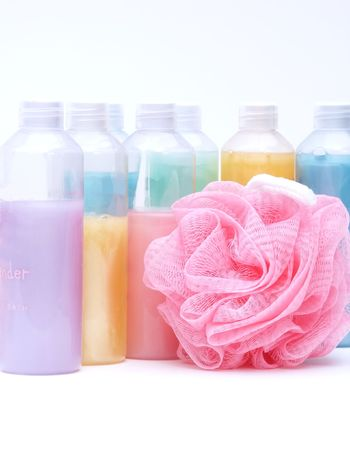 sooth: bath supplies in a rainbow of pastel colors with pink bath poof. Vertical on white. Stock Photo