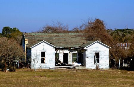 damaged roof: Damaged house with roof caving in and missing windows could illustrate storm or fire damage remodeling insurance needs etc