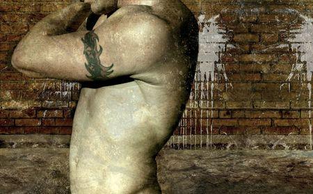 graffiti brown: Bad Boy  tribales brazo con un tatuaje en el torso desnudo contra un joven de fondo grunge Foto de archivo