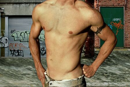 body paint sexy: Shirtless young male with tribal tattoo in a grunge alleyway Stock Photo