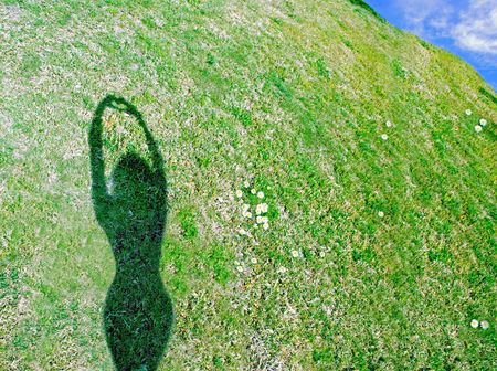 Shadow of woman on hillside making heart shape with hands