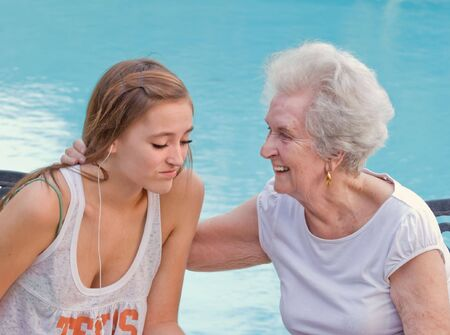 Grandmother comforts and advises granddaughter Stock Photo