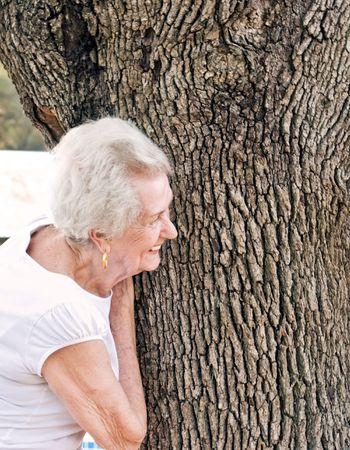face in tree bark: Happy Senior Woman Stock Photo