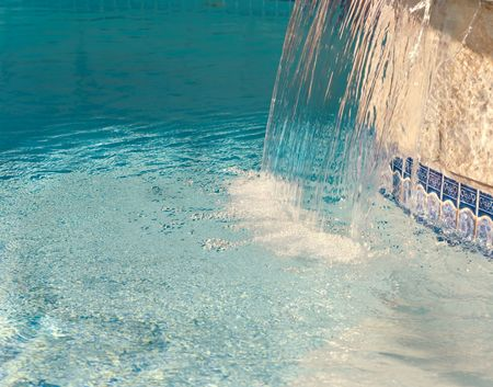 Cool water splashing down from a hot tub into a pool Stock Photo