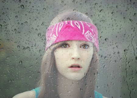 Beautiful sad girl seen through a rainy window photo