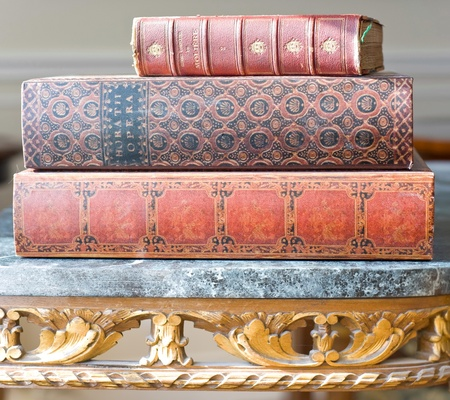Old leatherbound books on an ornate antique library table Archivio Fotografico