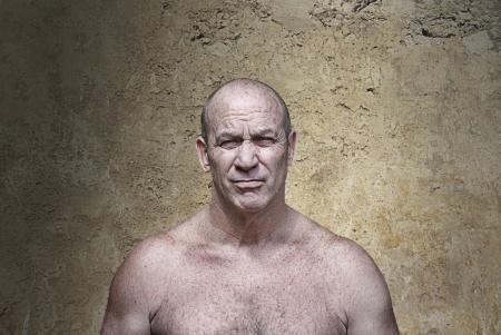 Gespierde boze man in agressieve houding in de voorkant van een betonnen muur