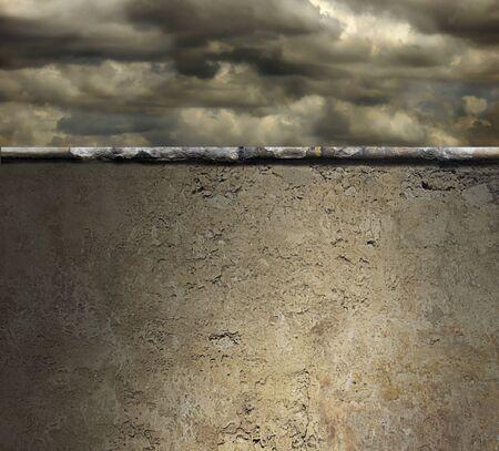 Atmosferische stormachtige hemel boven een hoge betonnen muur Stockfoto