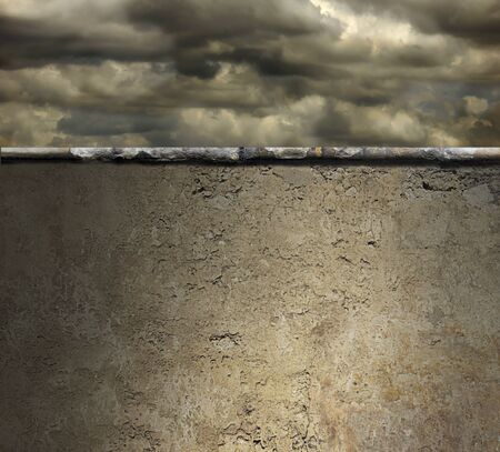 Atmospheric stormy sky above a high concrete wall
