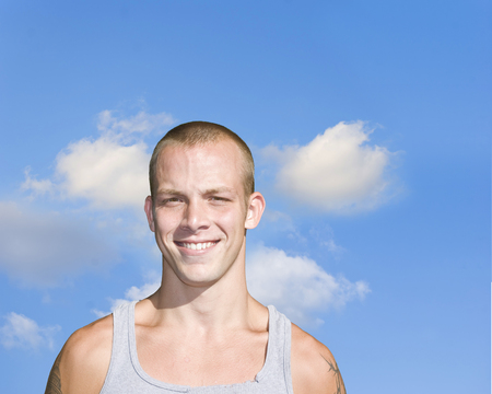 A good-looking young blond guy smiling under a blue sky photo