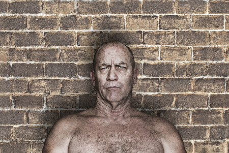 Big menacing shirtless man against a brick wall