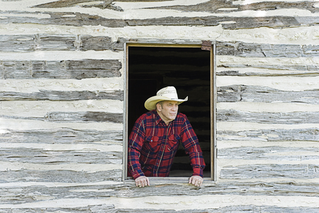 Handsome cowboy or rancher looking off into the distance from a rustic window
