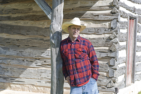 quizzical: Handsome rugged cowboy outside a log cabin Stock Photo