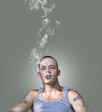 Handsome cocky young guy smoking a cigarette Stock Photo