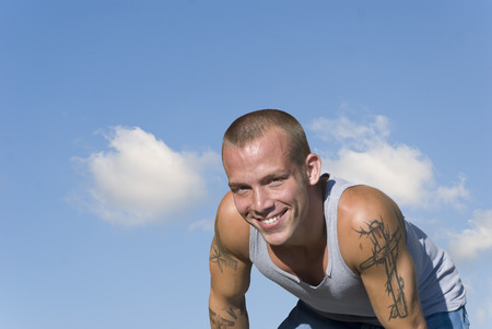 Handsome blond guy with tattoos smiling under a sunny blue sky Stock Photo