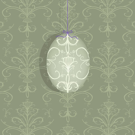 Pretty decorated Easter egg suspended on a taupe damask background