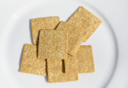 Whole grain crackers on a white plate Stock fotó