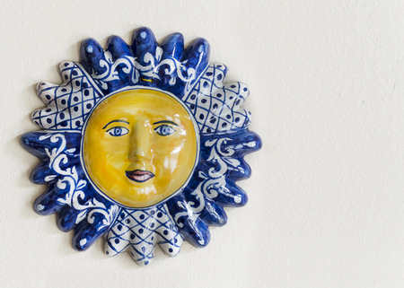 Colorful Mexican hand-painted Talavera ceramic sun face hanging on a wall