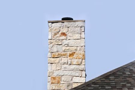 Limestone chimney on a shingle rooftop