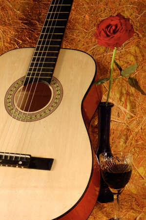 guitar, rose, wine on a straw background Stock Photo - 924256