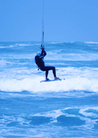 Jumping kite surfer on blue background
