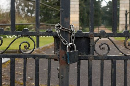safekeeping: A Lock and Chain on Metal Fence Gate to the Road