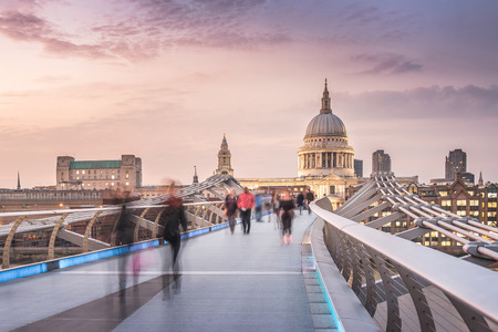 city of london: The Millennium Bridge to the St Pauls Cathedral in Twilight with Moving People Stock Photo