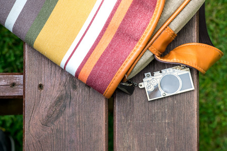 keychain: Colorful Side Bag placed on the Wood Bench with Wooden Camera Keychain attached on Green Grass Stock Photo