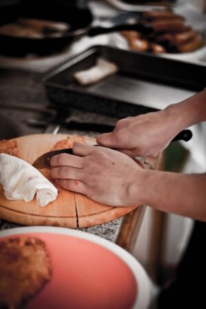 everyday scenes: cooker handle knife slicing food in the kitchen table Stock Photo