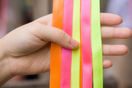 a hand is holding some colorful ribbon photo