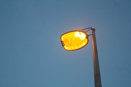 yellow street lamp on blue sky background
