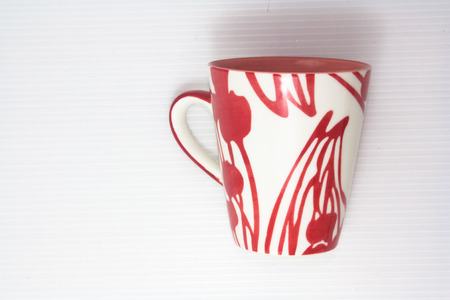 tall cup with handle decorated with red pattern